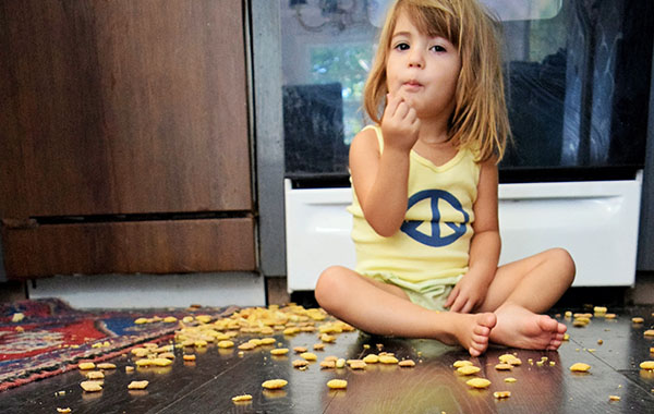 young girl sits on hardwood kitchen floor snack spilled on floor
