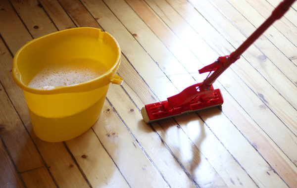 Cleaning wooden floor with a mop