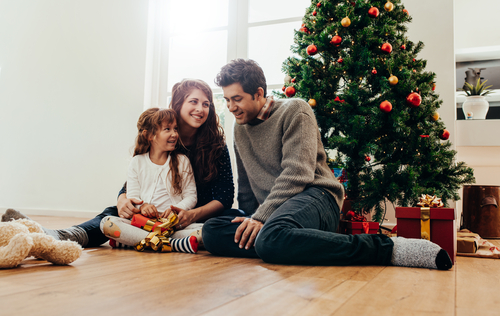 family sitting beside christmas tree